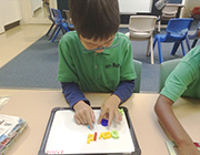 Student writing using magnetic letters